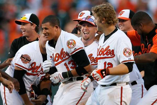 The Baltimore Orioles' Manny Machado gets mobbed by