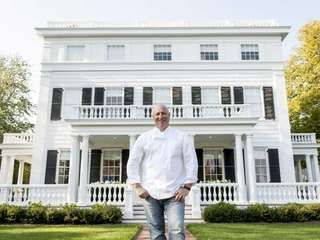 Tom Colicchio stands outside Topping Rose House, a