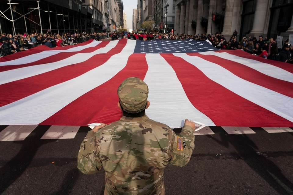 A soldier holds an American flag during the