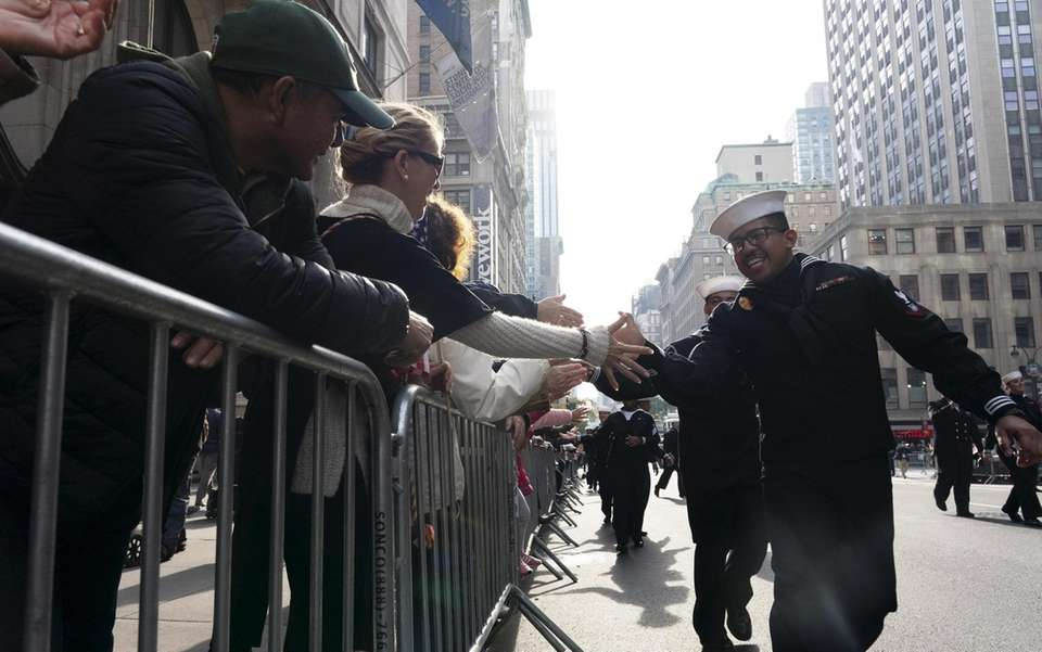 Sailors high-five spectators during the New York City