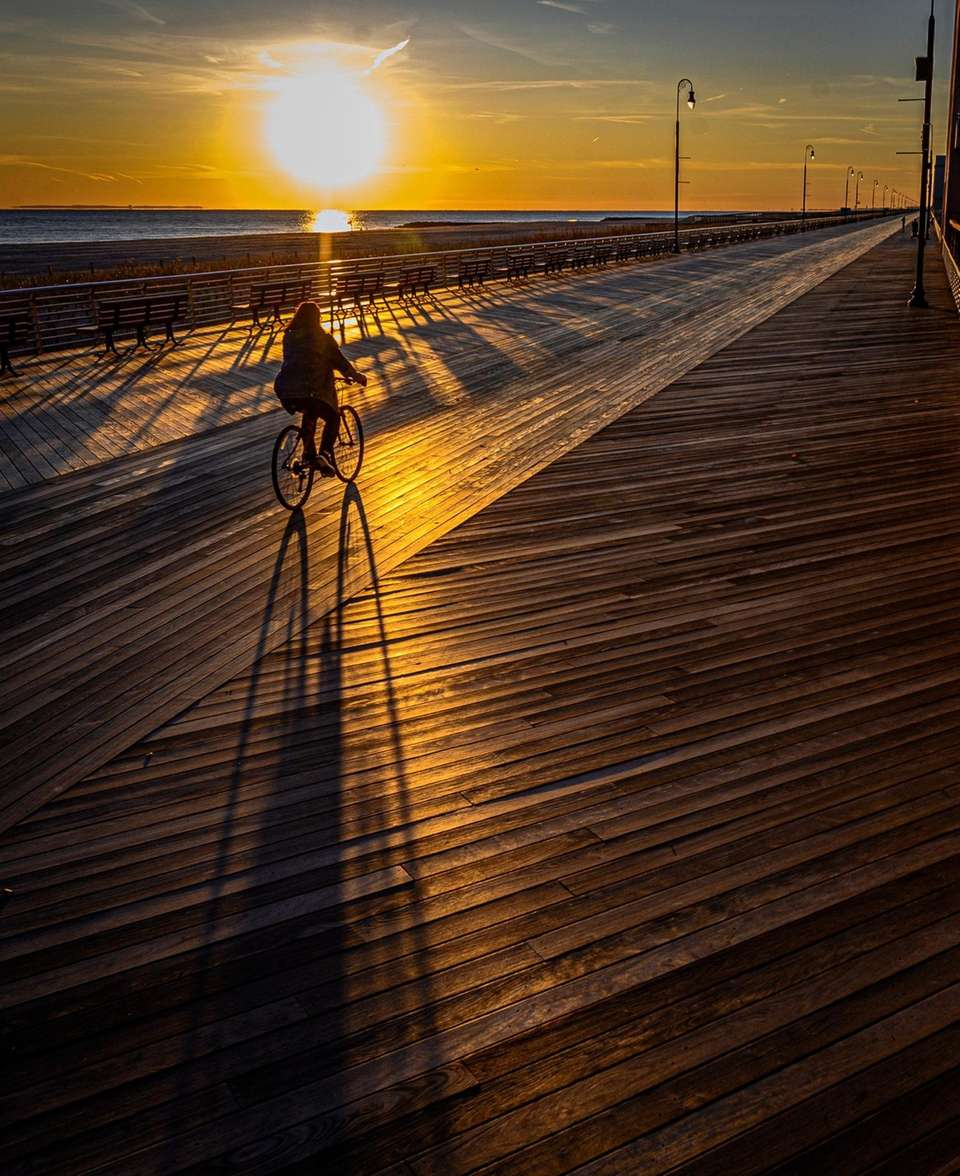 A woman riding her bike on the boardwalk
