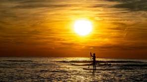 Long Beach resident Brendan McDerby paddle boarding off