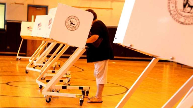 A resident casts a vote at a polling