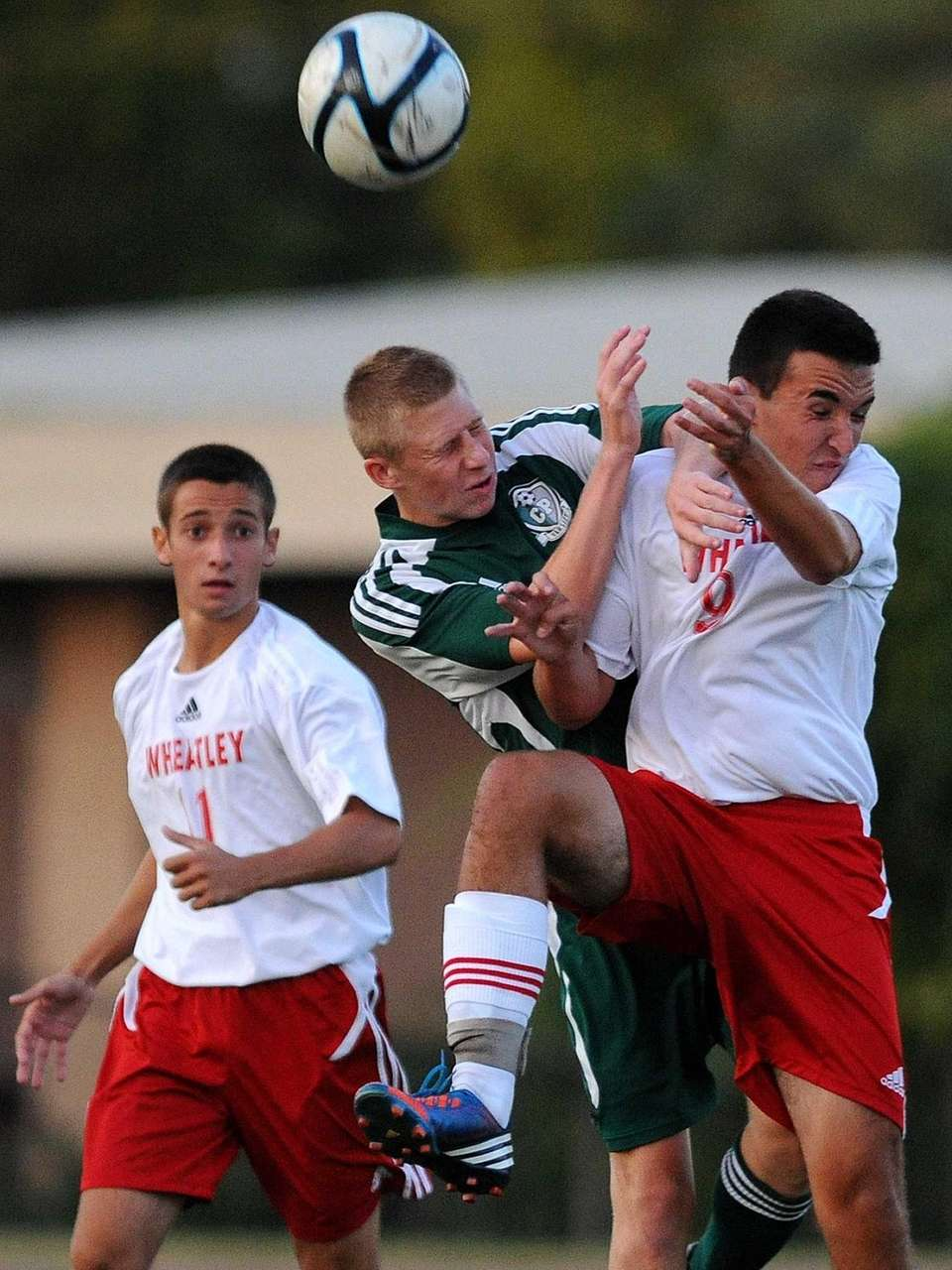 Carle Place High School's Mike Montello, center, tries