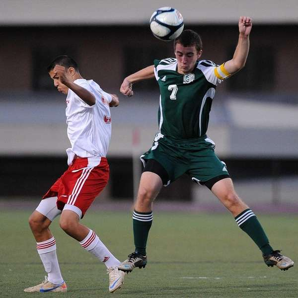 Carle Place's Matt Carr, right, heads a ball