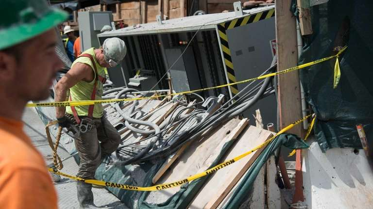 Construction workers clear debris at 72nd Street after