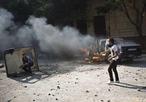 Egyptian protesters throw stones during clashes near the