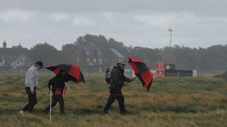 Spectators wait in bad weather for play to