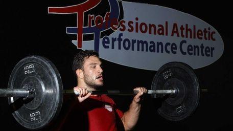 Mixed martial artist Gian Villante lifts weights during