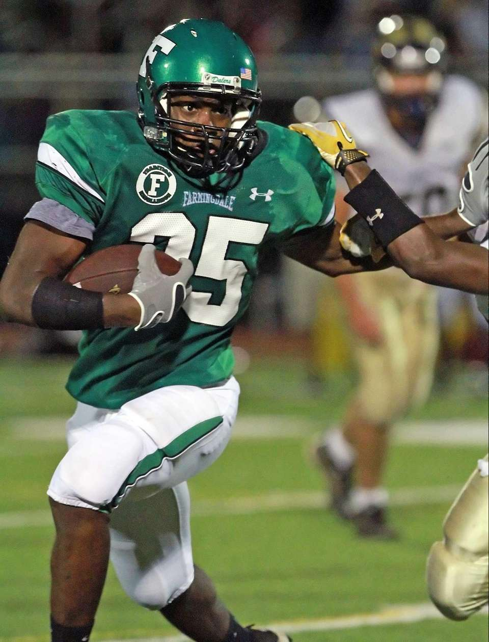 Farmingdale's Kevin Petit-Frere stiff arms a defender during
