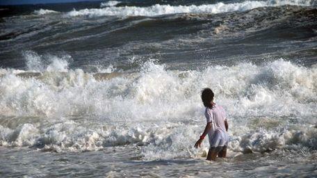 People brave the rough surf at Jones Beach