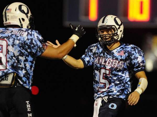 Oceanside High School receiver Anthony Pintabona, right, gets