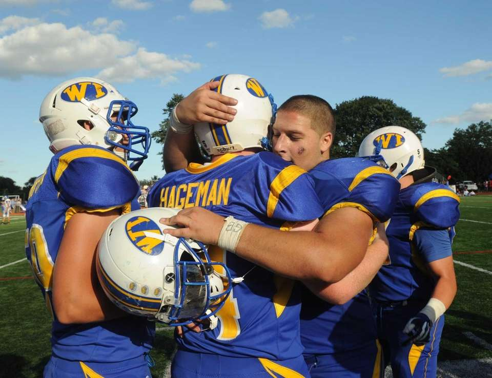 Zach Hageman of West Islip, center, is hugged
