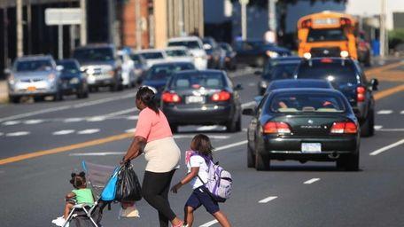 Pedestrians cross Hempstead Turnpike in the middle of