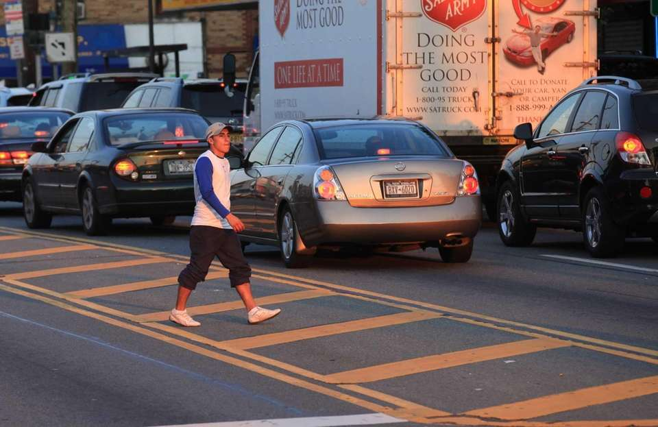 Pedestrians cross Hempstead Turnpike at Plainfield Road in