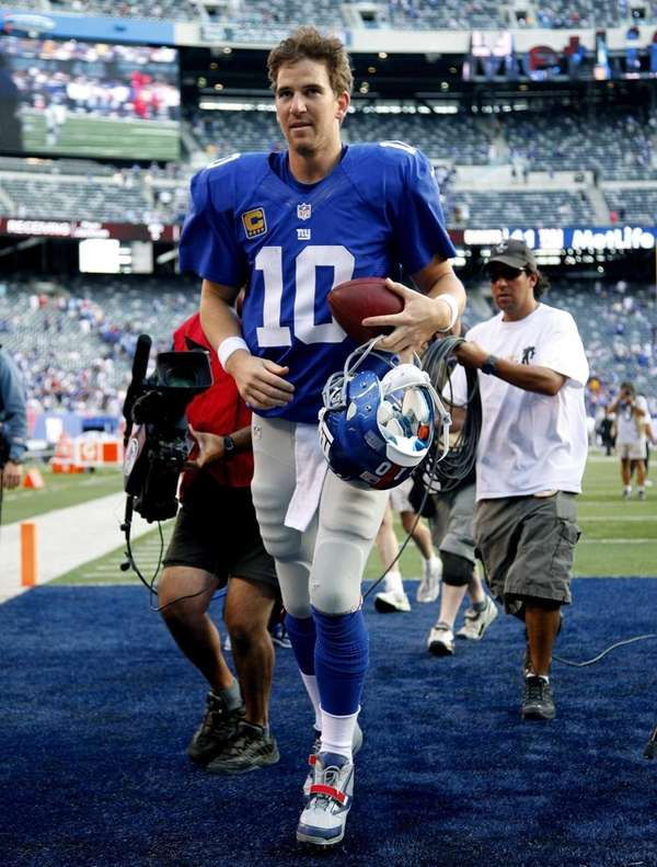Eli Manning runs off the field after a
