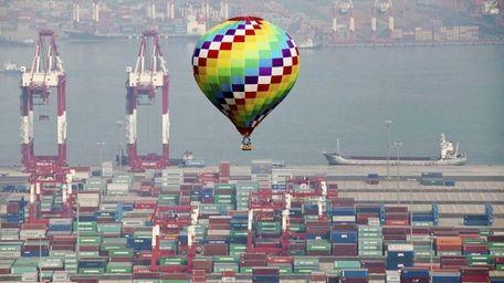 A hot-air balloon flies over a container port