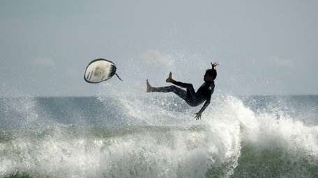 A wave topples a surfer at Ditch Plains