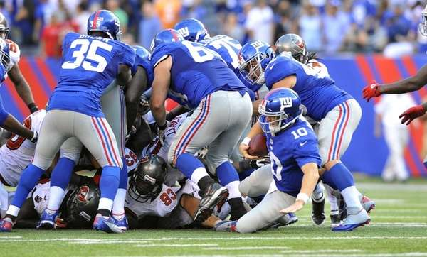Eli Manning is knocked down as he took