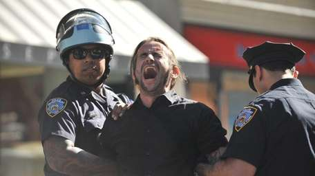 An Occupy Wall Street supporter is restrained by