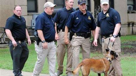 Officers with a dog after searching Evangeline Hall