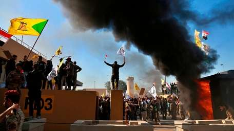 Supporters of an Iran-backed Iraqi Shia militia burn