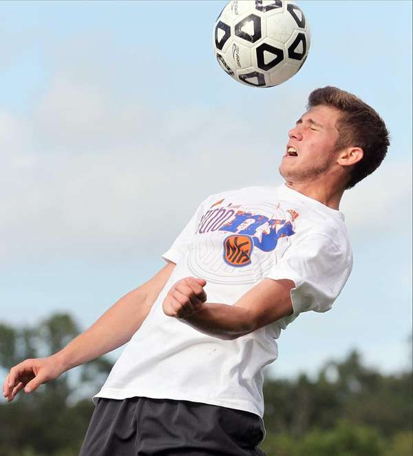 Jericho's Zach Cohen heads a ball during boy's