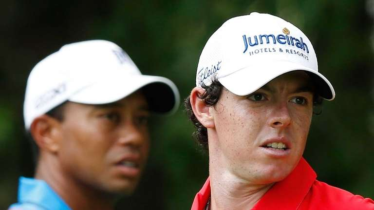 Tiger Woods, left, and Rory McIlroy wait on