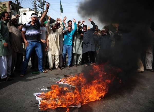 Pakistani Muslims shout anti-U.S. slogans beside burning U.S.