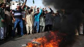 Pakistani Muslims shout anti-U.S. slogans beside burning U.S.