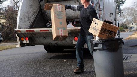 A sanitation worker picks up garbage in Brookhaven