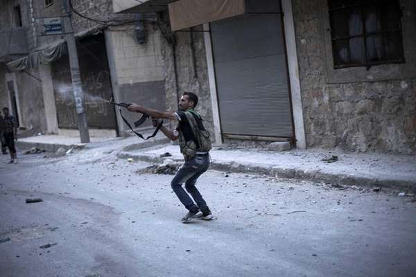 A Free Syrian Army fighter fires his weapon