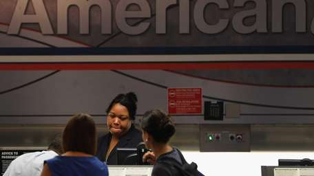 An American Airlines employee helps travelers at the