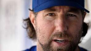Mets pitcher R.A. Dickey talks in the dugout