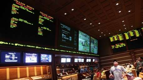 Sports bettors watch the screens in the race
