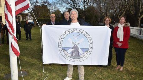 Artist Scott Bluedorn holds a flag adorned with