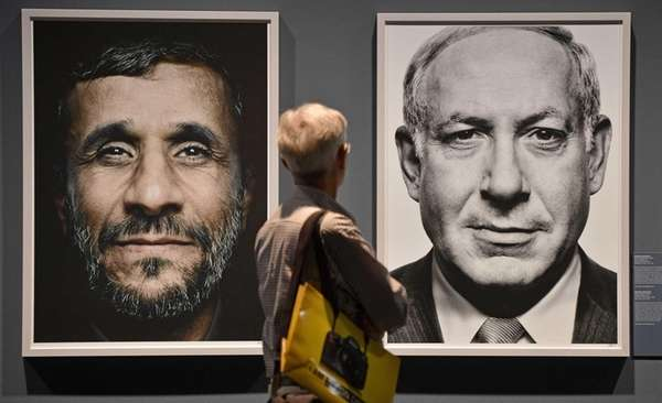 A visitor looks at portraits of Iran's President