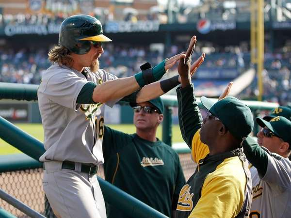 Josh Reddick celebrates with teammates after scoring in