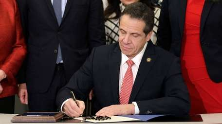 New York Gov. Andrew M. Cuomo signs the