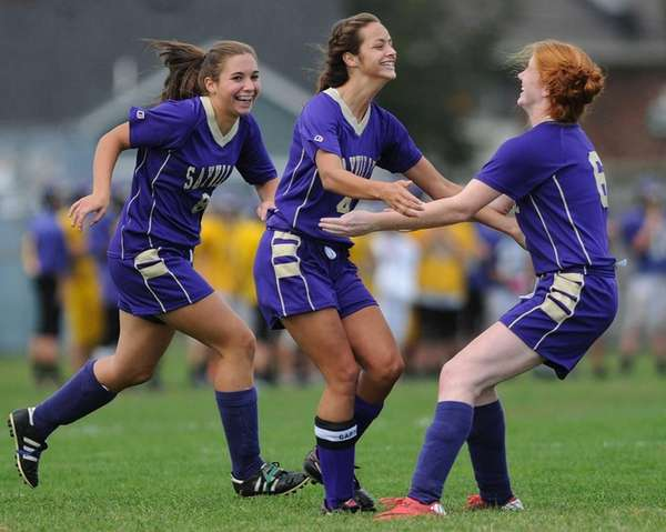 Sayville's Madison Hoon, center, gets congratulated by teammates