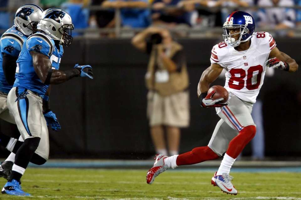 Victor Cruz runs after a catch as Carolina