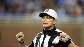 Referee Ed Hochuli (85) signals during the second