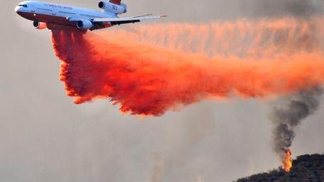 A DC-10 tanker drops fire retardant on a