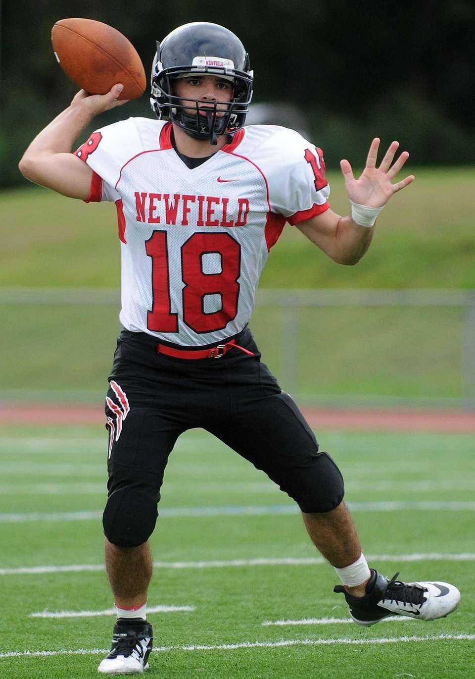 Newfield's quarterback Brandon Riggi throws a pass during