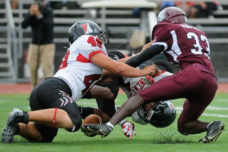 Newfield's Terrell Perryman, center, recovers a Whitman fumble