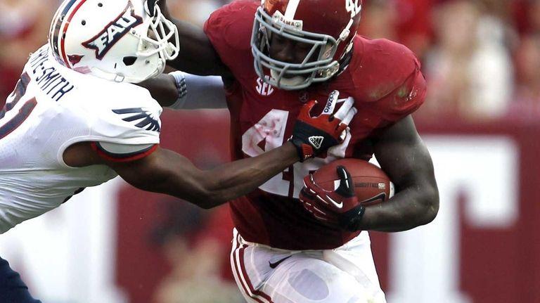 Alabama running back Eddie Lacy stiff-arms Florida Atlantic
