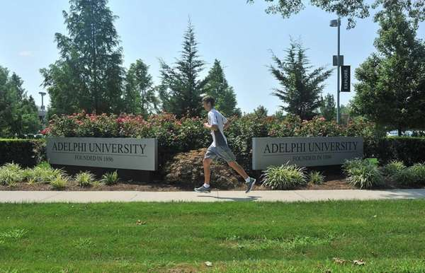 A runner trots past the Adelphi University signs