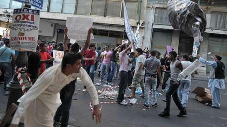 Muslim protesters throw garbage towards riot police, during