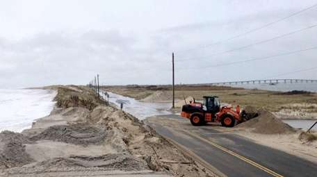 Sand is removed from Dune Road near the