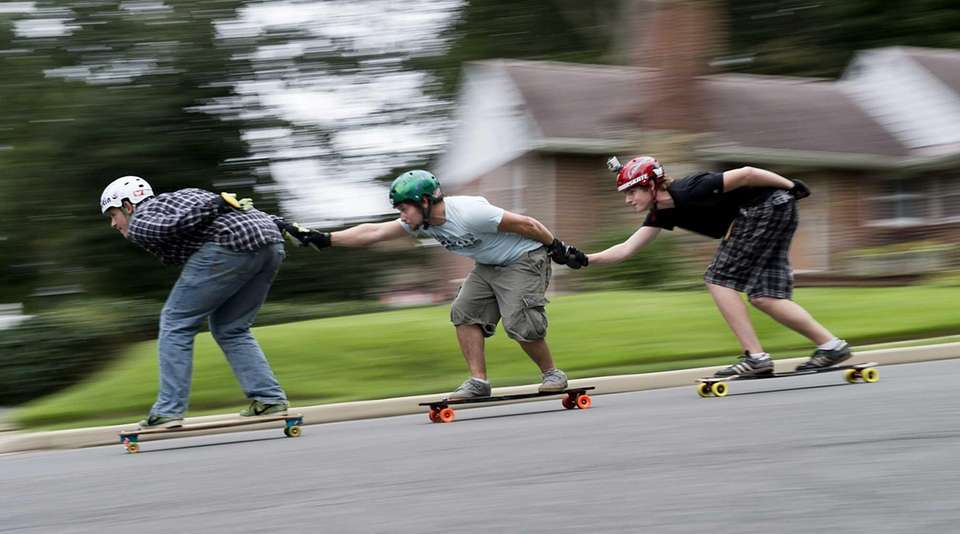 Three skateboarders enjoy the short hill on Fairview